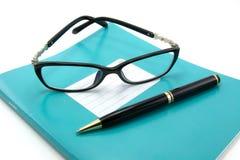 Taccuini, penne, vetri Fotografie Stock