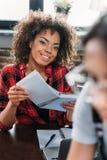 Taccuino afroamericano sorridente della tenuta della donna mentre sedendosi alla tavola Immagini Stock Libere da Diritti
