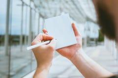 Taccuino alto falso in mano di un uomo, contro lo sfondo di una costruzione di vetro fotografie stock libere da diritti
