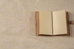 Taccuino aperto che si trova su una superficie della tela di sacco Fotografia Stock