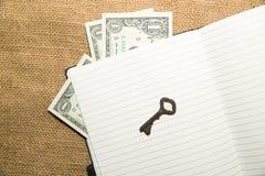 Taccuino aperto, chiave e soldi sul vecchio tessuto Immagini Stock
