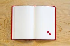 Taccuino aperto con cuore rosso su fondo di legno immagini stock libere da diritti