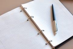 Taccuino aperto con la penna che si trova su sul desktop beige Strati del blocco note sui sostegni d'argento, penna a sfera autom fotografie stock