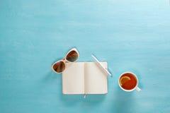 Taccuino aperto con la penna, tazza di tè ed occhiali da sole sulla tavola di legno blu Vista superiore Scrittura, concetto di bl Fotografia Stock