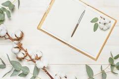 Taccuino aperto con le pagine in bianco, la penna, il ramoscello dell'eucalyptus ed i fiori del cotone sulla disposizione piana d fotografia stock libera da diritti
