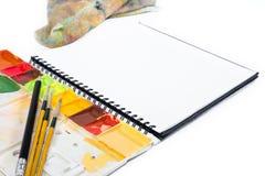 Taccuino aperto del primo piano con i colori del vassoio su fondo fotografia stock libera da diritti