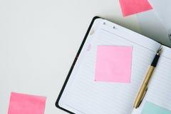 Taccuino aperto, penna e Post-it di vista superiore sul fondo bianco dello scrittorio Fotografia Stock