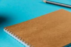 Taccuino in bianco con la matita e la tazza di caffè su fondo blu workplace Copi lo spazio fotografia stock