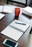Taccuino in bianco con la penna e smartphone con la tazza di caffè sul ripiano del tavolo Immagini Stock Libere da Diritti