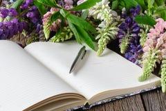 Taccuino in bianco con la penna ed il mazzo della tavola di legno dei fiori concetto di scrittura del diario Fotografia Stock Libera da Diritti