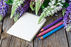 Taccuino in bianco con la penna ed il mazzo della tavola di legno dei fiori concetto di scrittura del diario Immagini Stock