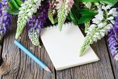 Taccuino in bianco con la penna ed il mazzo della tavola di legno dei fiori concetto di scrittura del diario Immagine Stock Libera da Diritti