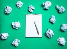 taccuino bianco con la penna su un fondo verde fra le palle di carta Il concetto di generazione delle idee, inventante le nuove i immagini stock