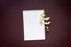Taccuino in bianco con un ramo di un gelsomino di fioritura su una porpora Immagine Stock