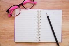 Taccuino in bianco con una matita e gli occhiali Fotografia Stock