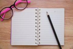 Taccuino in bianco con una matita e gli occhiali Fotografia Stock Libera da Diritti