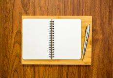 Taccuino in bianco con una penna su fondo di legno Fotografie Stock Libere da Diritti