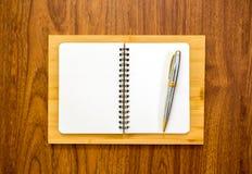 Taccuino in bianco con una penna su fondo di legno Fotografia Stock