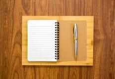 Taccuino in bianco con una penna su fondo di legno Immagini Stock