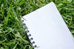 Taccuino in bianco nel fondo fresco dell'erba verde fotografie stock libere da diritti