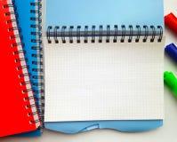 Taccuino in bianco per la scuola con le penne di indicatori Pila di taccuini variopinti isolati su fondo bianco Blu, rosso, verde fotografia stock