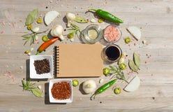 Taccuino in bianco per le note e pepe, foglia di alloro, rosmarino, cipolle, sale himalayano, olio d'oliva, salsa di soia su un d Fotografia Stock