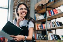 Taccuino caucasico sorridente e distogliere lo sguardo della tenuta della donna biblioteca Immagini Stock Libere da Diritti