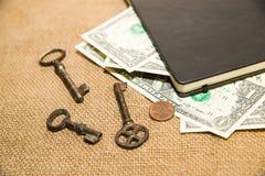 Taccuino, chiave e soldi sul vecchio tessuto Fotografia Stock Libera da Diritti