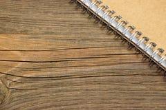 Taccuino chiuso con la copertina di carta di Brown sulla Tabella rustica di legno immagini stock libere da diritti