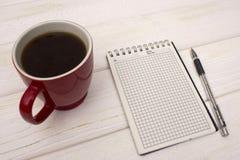 Taccuino con caffè su una tavola di legno Fotografia Stock