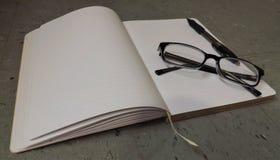 Taccuino con i vetri di lettura e penna sulla cima fotografie stock