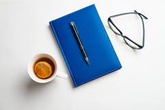 Taccuino con i vetri e la penna, libro con i vetri, taccuino blu fotografie stock