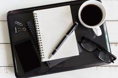 Taccuino con il computer portatile e la tazza di caffè sullo scrittorio di legno Immagini Stock Libere da Diritti