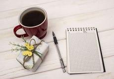 Taccuino con il contenitore di regalo e di caffè su una tavola di legno Immagini Stock Libere da Diritti