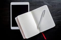 Taccuino con il segnalibro rosso su una tavola scura con una penna e un computer bianco della compressa Fotografie Stock Libere da Diritti