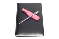 Taccuino con la penna rosa del metallo e dell'indicatore Fotografia Stock Libera da Diritti