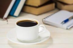 Taccuino con la penna su una tavola di legno davanti alla finestra Una tazza di caffè caldo sulla tabella Immagini Stock Libere da Diritti