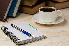 Taccuino con la penna su una tavola di legno davanti alla finestra Una tazza di caffè caldo sulla tabella Una pila di libri Immagine Stock