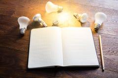 Taccuino con le lampadine d'ardore sullo scrittorio di legno Fotografia Stock
