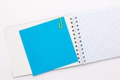 Taccuino con un foglio blu di carta colorata con una carta gialla Fotografie Stock