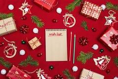 Taccuino con una lista di obiettivi e una composizione di Natale dei regali e decorazione sul fondo rosso del tessuto immagini stock