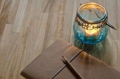 Taccuino con una vecchia lanterna della candela Fotografie Stock