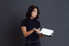 Taccuino confuso della tenuta della giovane donna in mani Fotografia Stock
