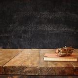 Taccuino d'annata e pila di matite variopinte di legno sulla tavola di legno di strutture contro il fondo della lavagna Immagini Stock