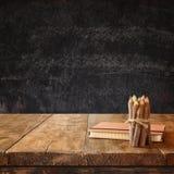 Taccuino d'annata e pila di matite variopinte di legno sulla tavola di legno di strutture contro il fondo della lavagna Immagine Stock