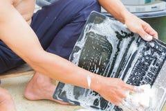 Taccuino del computer di pulizia del primo piano con il sapone di lavaggio del piatto, techn fotografia stock