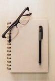 Taccuino di Brown con gli occhiali e penna nera su fondo di legno fotografia stock libera da diritti
