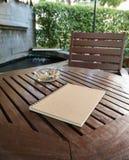 Taccuino di Brown sulla tavola di legno nel giardino fotografia stock libera da diritti