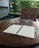 Taccuino di Brown sulla tavola di legno nel giardino immagine stock libera da diritti