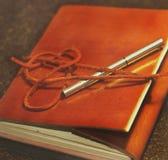 Taccuino di cuoio del Brown con la penna del materiale di riempimento Immagini Stock